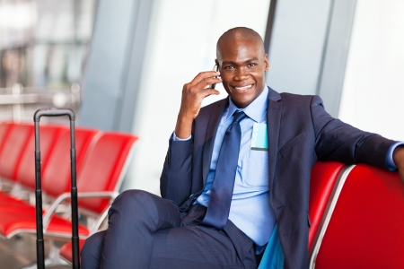 business traveler: african business traveler talking on cell phone at airport Stock Photo
