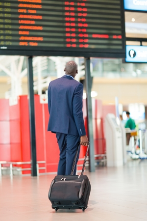 black business men: african businessman with luggage looking at flight information board in airport Stock Photo