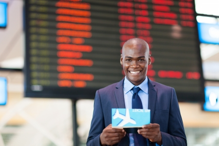 business traveler: african business traveler in front of flight infomation board in airport Stock Photo