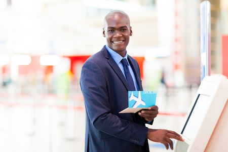 check in: african businessman using self service check in machine in airport