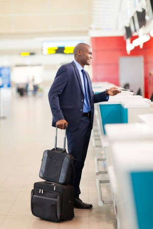 business traveller: african businessman standing by airport check in counter