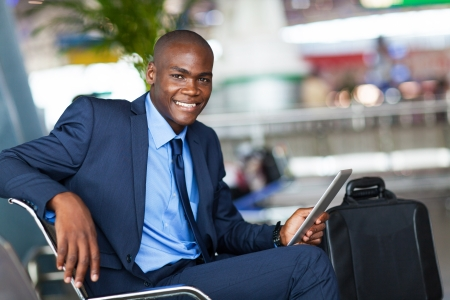 corporate travel: handsome african businessman using tablet computer in airport