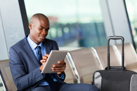 business traveler: black businessman using tablet computer at airport
