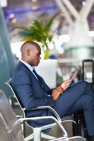african american businessman using tablet computer at airport photo