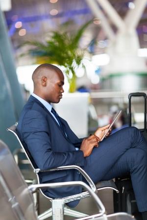 Afro-Amerikaanse zakenman met behulp van tablet-computer op de luchthaven