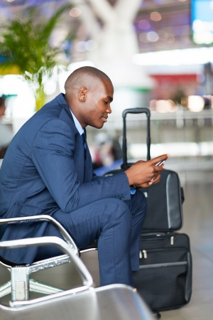 african businessman using cell phone at airport photo