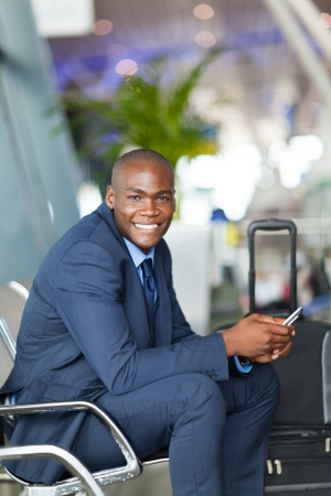 happy male african business traveller in airport waiting for flight photo