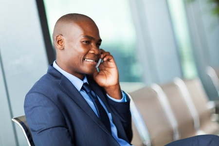 african american talking on cell phone at airport photo