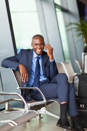 african business traveller talking on mobile phone in airport photo