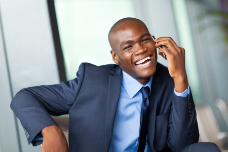 happy african corporate worker talking on cell phone in modern office photo