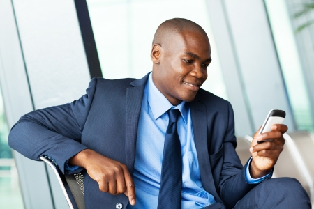 handsome african american businessman using smart phone emailing photo