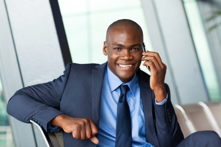 african business traveller talking on cellphone in airport photo