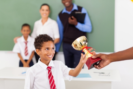 elementary school boy receiving a trophy in classroom with teachers and classmate Stock Photo - 18417341