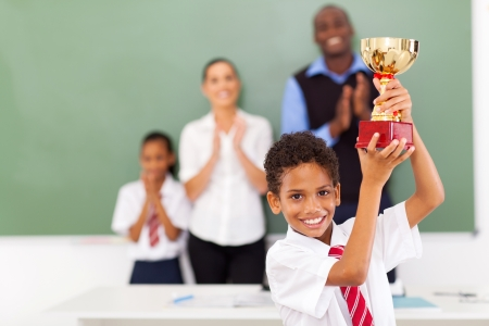 happy male elementary school student holding a trophy in classroom photo
