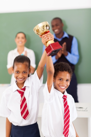 people clapping: two elementary students holding a trophy in classroom