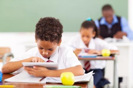 niños estudiando: colegial lindo elemental utilizando un equipo Tablet PC en el aula