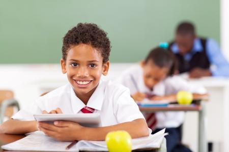 ni�os en la escuela: ni�o de la escuela primaria que usa la tableta inform�tica en el aula Foto de archivo