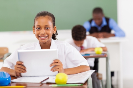 african education: primary schoolgirl using a tablet computer in classroom