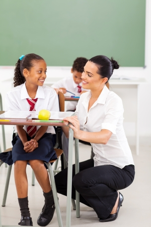 primary schoolgirl and teacher communicating during a lesson photo