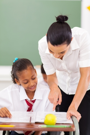 educators: hermosa hembra educador primario estudiante de tutoría en la escuela