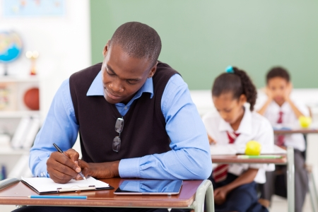 grading: African American primary school teacher preparing a lesson in classroom Stock Photo