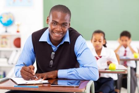 estudiantes adultos: Profesor africano escuela primaria preparar una lección en el aula