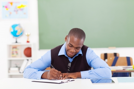 handsome African male teacher preparing a lesson in classroom photo
