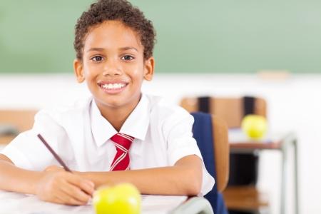 happy elementary schoolboy writing in classroom photo