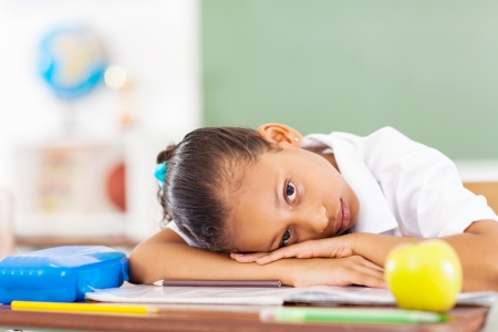 ni�os enfermos: colegiala primaria descansa sobre el escritorio