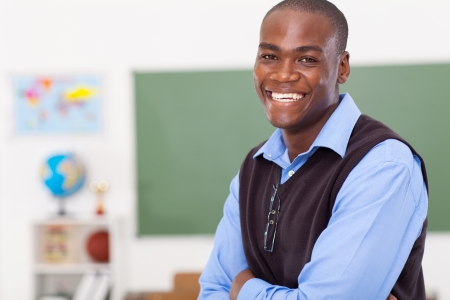 male teacher: handsome male african primary school teacher in classroom