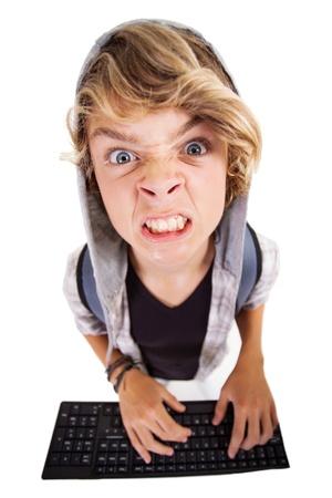 adolescencia: vista desde arriba de muchacho adolescente enojado que juega en el teclado de computadora