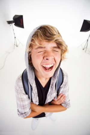 funny teen boy laughing in photographic studio photo