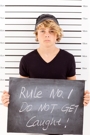 teen boy holding a blackboard criminal mug shot Stock Photo - 18562077