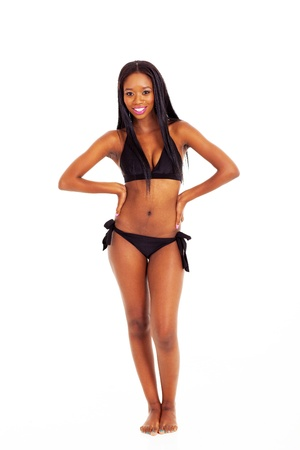 pretty young african woman in black bikini on white background photo