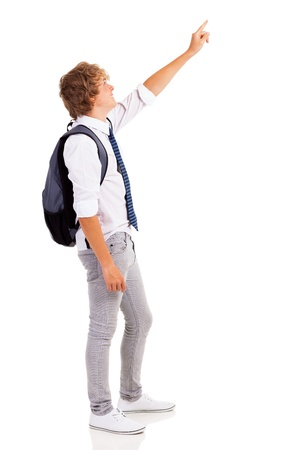 side view of teen boy pointing at empty copyspace photo