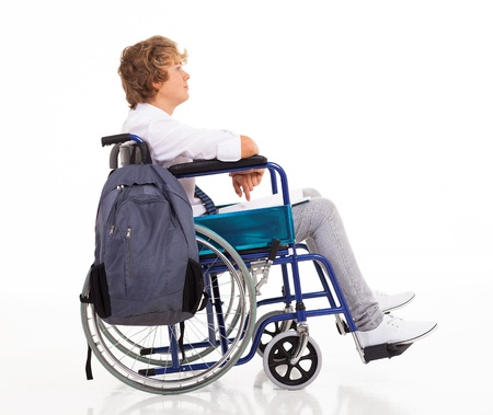 side view of handicapped teen boy sitting on wheelchair photo