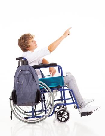 niño discapacitado adolescente sentado en silla de ruedas y que señala en el fondo blanco