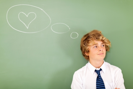 good looking teenage boy thinking about love in front of chalkboard photo