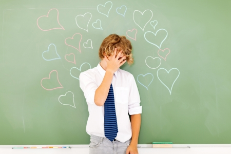 embarrassed: young teenage boy hide face because of love
