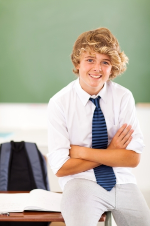 good looking teenage guy: middle school teen student sitting on desk in classroom Stock Photo