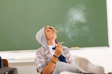 troublesome: bad high school teen student smoking in classroom