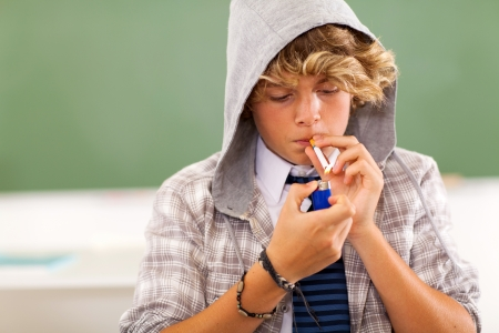 man smoking: bad high school teen boy lighting cigarette in classroom Stock Photo