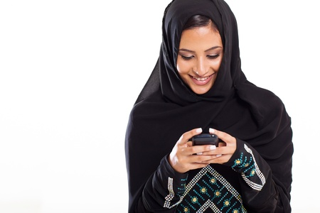 pretty modern Arabic woman playing on smart phone isolated on white photo