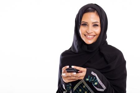 femme musulmane: jeune femme arabe avec téléphone intelligent isolé sur blanc