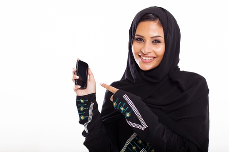 young middle eastern woman pointing at smart phone isolated on white photo