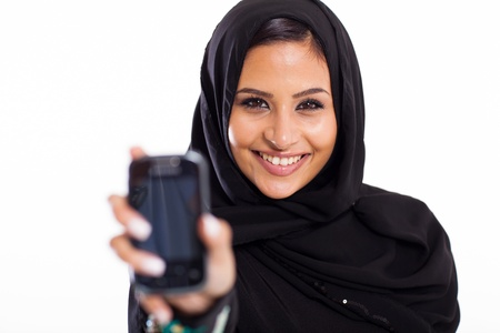 attractive muslim girl holding smart phone isolated on white photo