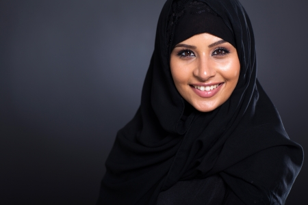 middle eastern ethnicity: smiling Arabic woman in traditional clothing on black background