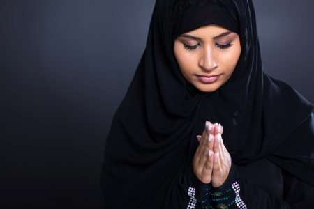 muslim: religious young Muslim woman praying over black background