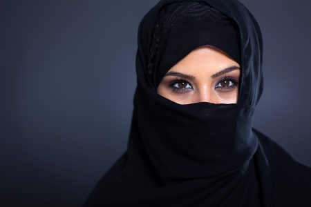 mysterious Arabian woman on black background photo