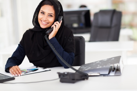 beautiful Arabian office worker talking on the phone photo